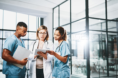 Buy stock photo Shot of a group of medical practitioners using a digital tablet together in a hospital
