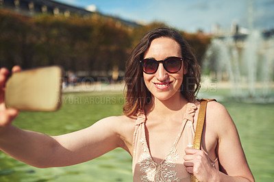 Buy stock photo Cropped shot of an attractive young woman taking selfies while exploring the city of Paris in France