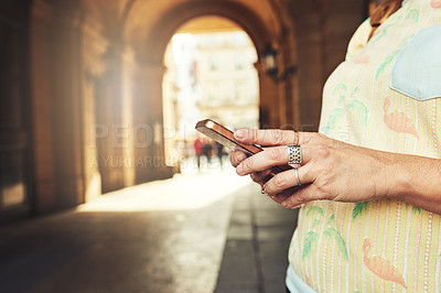 Buy stock photo Cropped shot of an unrecognizable young woman sending text messages while exploring the city of Paris in France