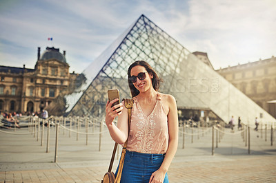 Buy stock photo Cropped shot of an attractive young woman taking selfies while exploring the city of Paris in France with the Louvre in the background