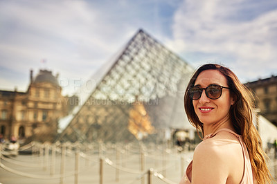 Buy stock photo Cropped portrait of an attractive young woman exploring the city of Paris in France with the Louvre in the background