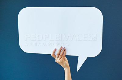 Buy stock photo Studio shot of an unrecognizable young woman holding up a sign against a blue background