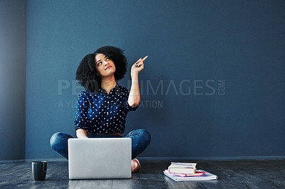 Buy stock photo Studio shot of an attractive young woman looking thoughtful while using a laptop against a blue background