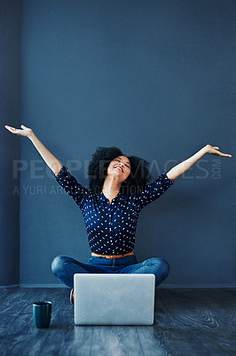 Buy stock photo Studio shot of an attractive young woman cheering while using a laptop against a blue background