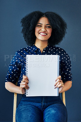 Buy stock photo Studio shot of a young woman holding up a blank notebook against a blue background
