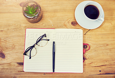 Buy stock photo High angle shot of a notebook and other various tools at a workstation