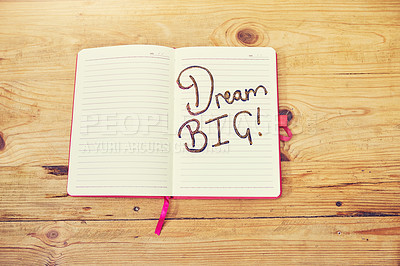 "Buy stock photo High angle shot of a creative workstation with a notebook that has the words ""dream big""written on it"