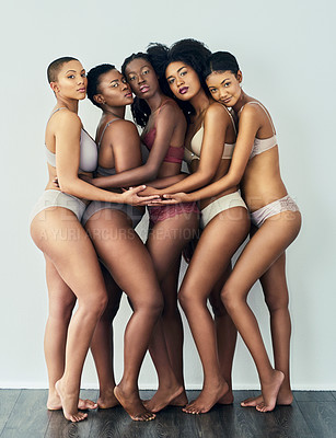Buy stock photo Studio shot of a group of beautiful young women posing together in their underwear against a grey background