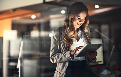 Buy stock photo Cropped shot of a young attractive businesswoman using a tablet while working late at night in the office