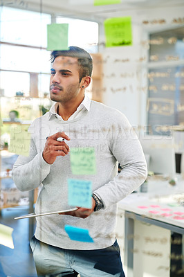 Buy stock photo Shot of a young businessman brainstorming on a glass wall in an office