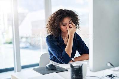 Buy stock photo Cropped shot of an attractive young businesswoman looking stressed while working at her desk in the office