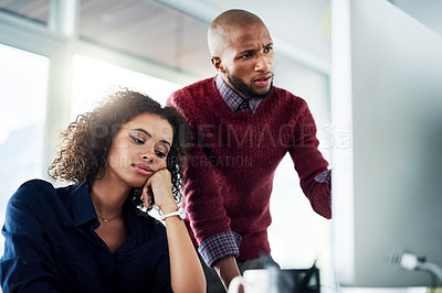 Buy stock photo Cropped shot of a male supervisor helping an uninterested young businesswoman while working in their office