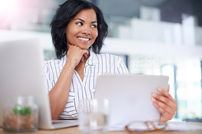 Buy stock photo Shot of a businesswoman using her digital tablet while sitting at her desk