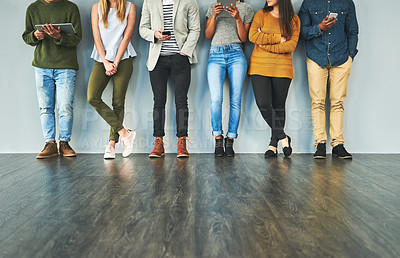 Buy stock photo Cropped shot of a group of unrecognizable young businesspeople using their wireless devices while standing in a row in their office