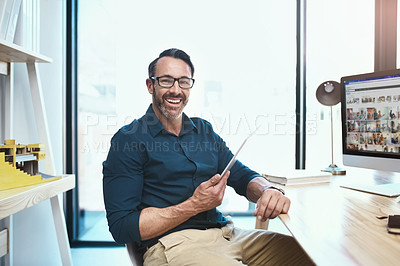 Buy stock photo Shot of a mature businessman using his digital tablet while sitting at his desk
