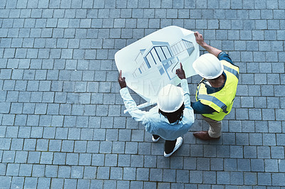 Buy stock photo High angle shot of two engineers looking at a blueprint