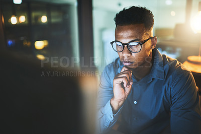 Buy stock photo Cropped shot of a handsome young businessman looking thoughtful while working late at night in a modern office