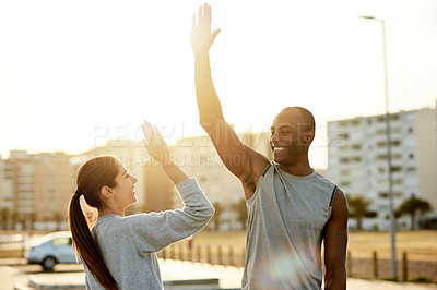 Buy stock photo Shot of a sporty young man and woman giving each other a high five while exercising outdoors