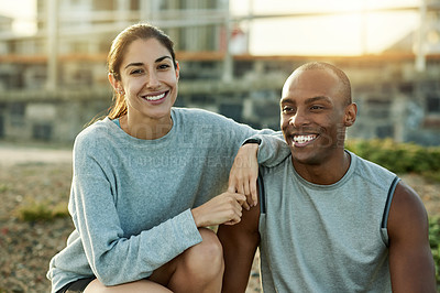 Buy stock photo Portrait of a sporty young man and woman taking a break while exercising outdoors