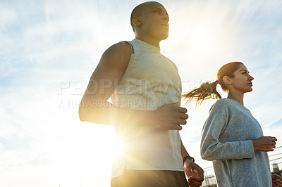 Buy stock photo Shot of a sporty young man and woman exercising together outdoors