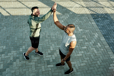 Buy stock photo High angle shot of two sporty men giving each other a high five while exercising outdoors