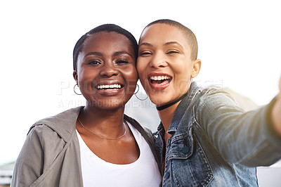 Buy stock photo Portrait of two young women smiling and posing while taking a selfie in the city