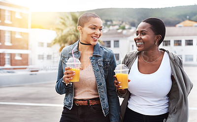 Buy stock photo Shot of two young women walking in the city laughing while holding their cool drinks