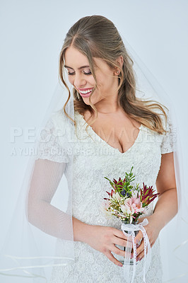 Buy stock photo Studio shot of a beautiful young bride holding a bunch of flowers on her wedding day against a gray background