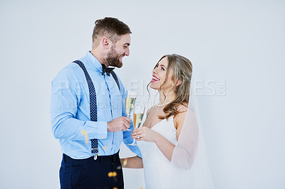 Buy stock photo Studio shot of a happy young couple having champagne on their wedding day against a gray background