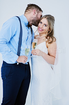 Buy stock photo Studio portrait of a happy young couple having champagne on their wedding day against a gray background