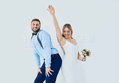 Buy stock photo Studio shot of a happy young couple dancing on their wedding day against a gray background