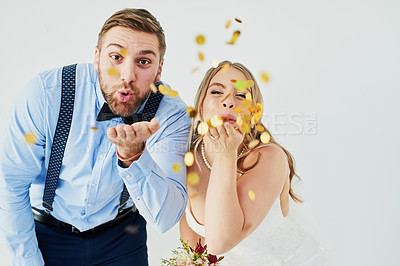 Buy stock photo Studio portrait of a happy young couple blowing confetti on their wedding day against a gray background