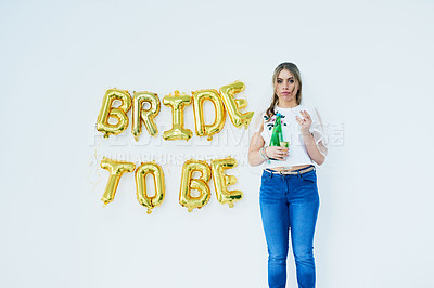 """Buy stock photo Studio portrait of a happy young woman celebrating her engagement with """"bride to be"""" in balloons on the wall"""