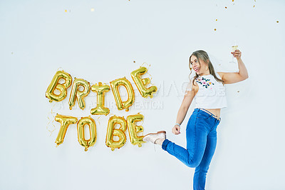 "Buy stock photo Studio shot of a happy young woman celebrating her engagement with ""bride to be"" in balloons on the wall"