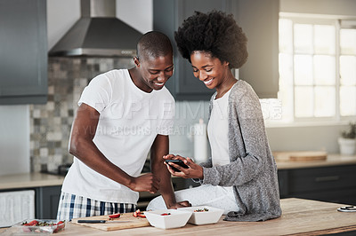 Buy stock photo Shot of a happy young couple using a mobile phone while preparing a healthy snack at home