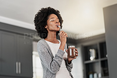 Buy stock photo Shot of a young woman eating chocolate from a jar at home