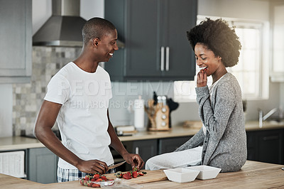 Buy stock photo Shot of a happy young couple snacking on strawberries together at home