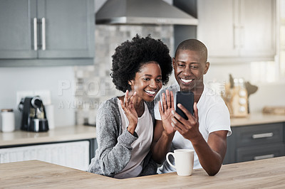 Buy stock photo Shot of a happy young couple using a mobile phone to make a video call at home