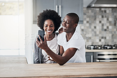 Buy stock photo Shot of a happy young couple using a mobile phone together at home