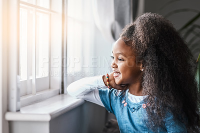 Buy stock photo Shot of an adorable little girl looking out the window at home