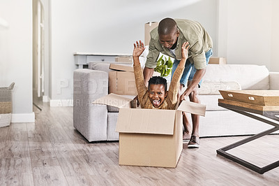 Buy stock photo Shot of a father pushing his son in a box while moving house