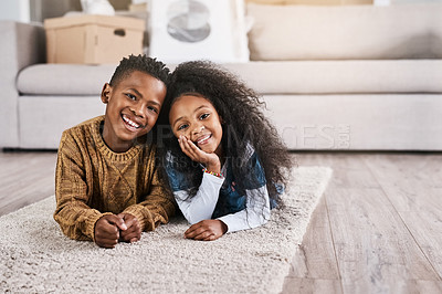 Buy stock photo Portrait of two adorable little siblings lying on a mat on the floor in the new home