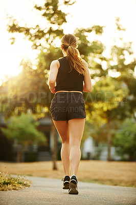 Buy stock photo Rearview shot of a sporty young woman exercising outdoors