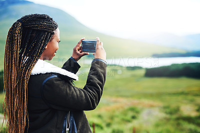 Buy stock photo Shot of a young woman capturing the beauty of nature on her cellphone