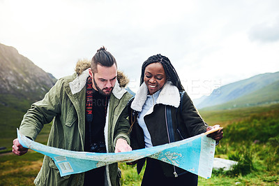Buy stock photo Shot of a young couple looking at a map while out exploring nature