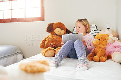 Buy stock photo Shot of an adorable little girl using a digital tablet while playing with her teddy bears at home