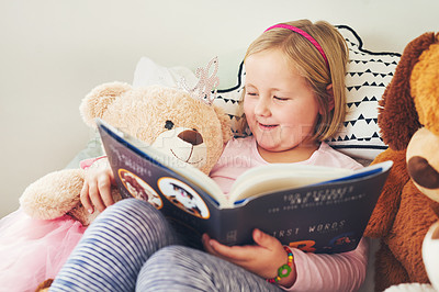 Buy stock photo Shot of an adorable little girl reading a book with her teddy bears at home