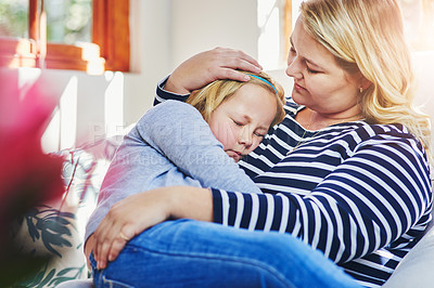 Buy stock photo Shot of a little girl sleeping in her mother's arms at home