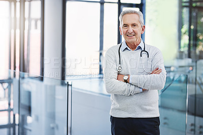 Buy stock photo Cropped portrait of a handsome mature male doctor standing with his arms folded in the hospital