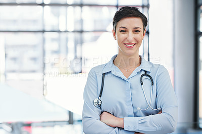 Buy stock photo Cropped portrait of an attractive young female doctor standing with her arms folded in the hospital